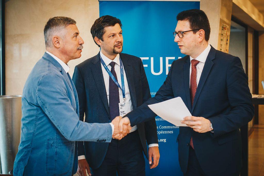 Tamás Sándor átadja a FUEN vezetőinek, Vincze Lóránt elnöknek és Daniel Alfreider alelnöknek a háromszéki civilek petícióját