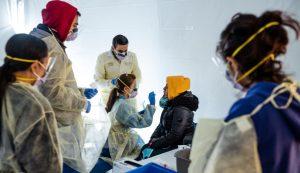 Orvosok COVID-19-tesztet végeznek az influenzatüneteket mutató kórházi személyzeten New Yorkban, március 24-én